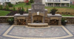 Outdoor fireplace with brick paver patio with custom inlay