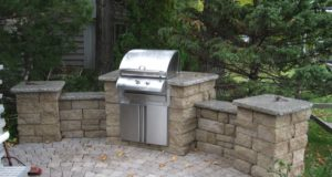 Outdoor kitchen with sitting walls & pillars with tumbled paver patio